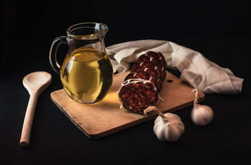 illuminated dark food photo of products of home slaughtering (salami, garlic, oil and wooden board) on black background. Traditional Slovak cuisine on dark background with decor.
