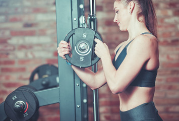 Fitness woman putting weight disk to barbell  against brick wall in gym