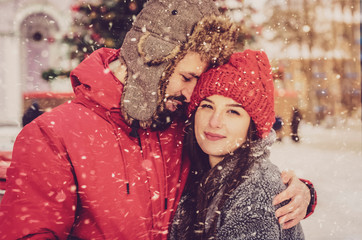 Happy Loving Stylish Couple kisses and hugs in the winter on the street near the Christmas tree. Beautiful man with beard and beautiful girl brunette model together
