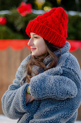 young, pretty model brunette poses for a photo in the winter near a Christmas tree in the middle of a winter city park, dressed in a red knitted hat and a warm gray coat and gloves