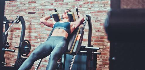 Sportswoman doing squatting in training machine at gym. Leg muscle training.