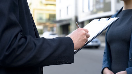 Businessman signing contract outdoors, female assistant waiting for document