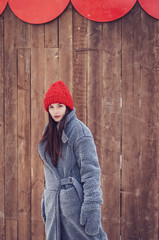 Outdoor portrait of elegant brunette woman wearing stylish red cap and warm coat. Space for text