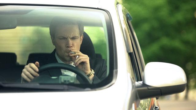 Upset man smoking nervously, sitting in car, bankruptcy, stress, divorce problem