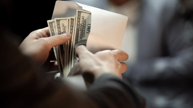 Envelope with dollars, lady giving bribe to politician to cover illegal business
