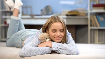 Happy lady hugging her teddy in bedroom, favorite toy, remembering childhood