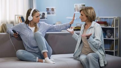 Girl in music headphones showing stop gesture to shouting mother, generation gap