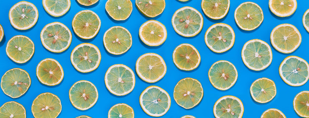 Wall Mural - Lemon slices in lines with hard shadows on blue background, flat lay image.
