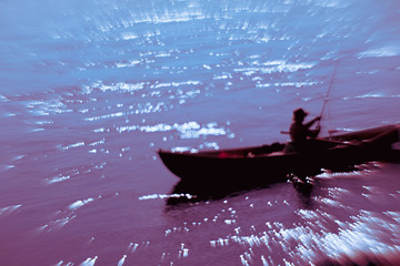 Blurred motion of fisherman sitting in boat in lake