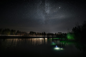 View of diving tower at lake against starry sky at night