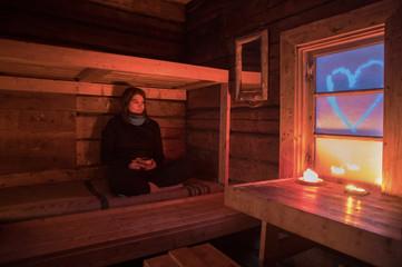 Woman sitting in log cabin