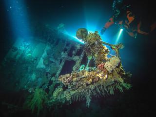 Male scuba diver exploring coral covered shipwreck in red sea