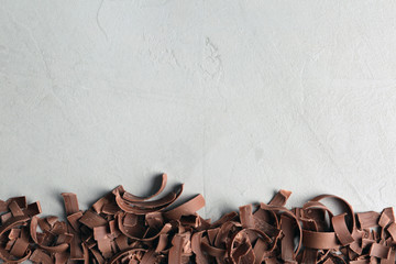 Chocolate curls and space for text on gray background, top view