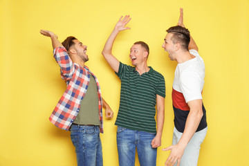 Group of friends celebrating victory against color background