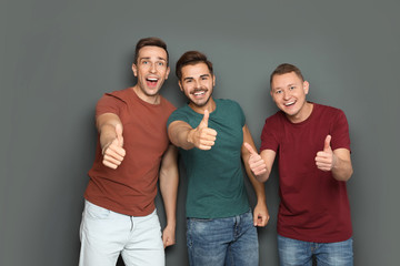 Group of friends celebrating victory against gray background