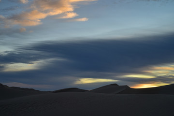early morning clouds over desert sand dunes of Imperial Sand Dunes, California, USA