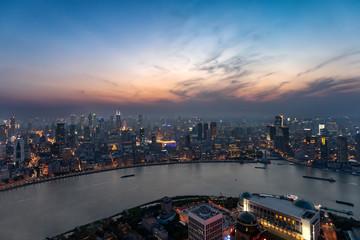 Blick auf die Skyline von Shanghai am Abend: der Bund am Huangpu Fluss mit den beleuchteten Wolkenkratzern