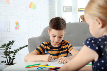 Cute little children drawing together at home