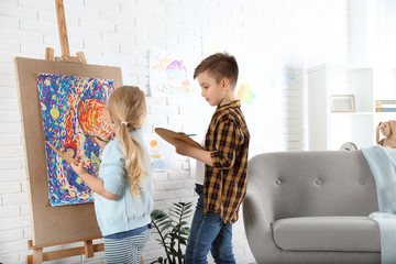 Cute little children painting on easel at home