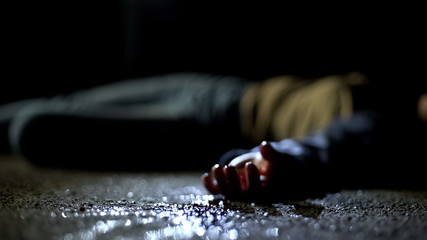 Close-up bloody body of young woman lying on ground, terrible killing, robbery Fototapete