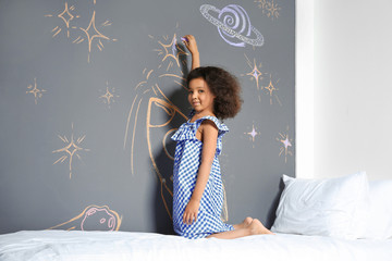 African-American child drawing rocket with chalk on wall in bedroom