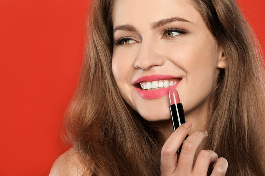 Young woman applying beautiful lipstick on color background