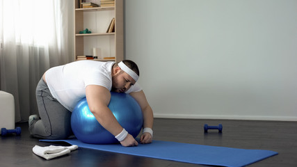 Chubby man resting after workout, lying on fitness ball, desire to lose weight