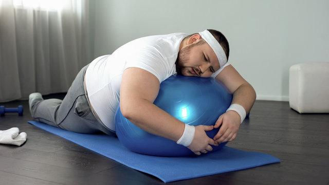 Weak-willed fat man relaxing on fitness ball, home workout break, laziness
