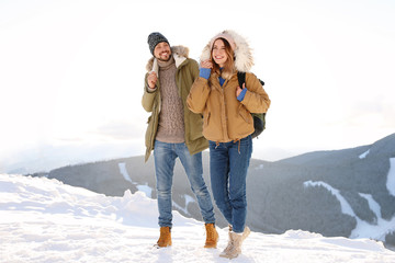 Happy couple spending winter vacation together in mountains