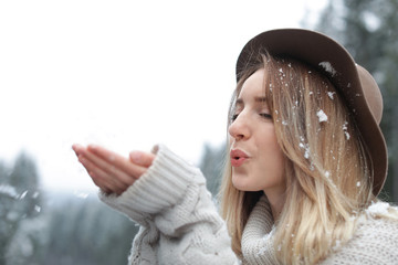 Young woman playing with snow outdoors. Winter vacation