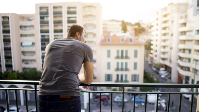Man enjoying view from his hotel suite balcony on busy street, business trip