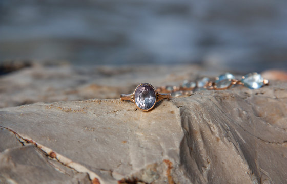 Ring with a large stone alexandrite lies on a rock by the sea