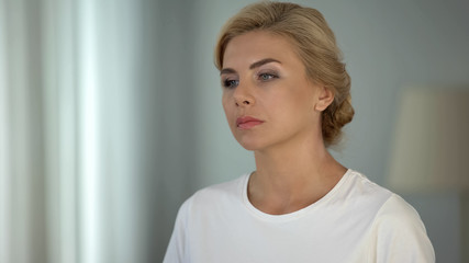 Beautiful blond-haired pensive lady thinking about life, depression and problems