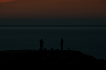 silhouette of a couple at sunset with the sea in the background