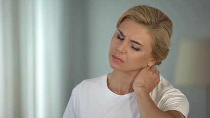 Good-looking blond woman suffering neck pain, sedentary life, health problems