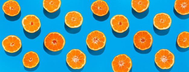 Mandarin halves in lines with hard shadows on blue background, flat lay image.