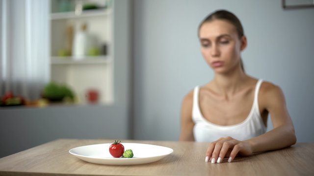 Exhausted slim woman looking at small portion of breakfast, self-destruction