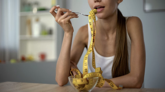 Calorie counting concept, thin girl eating measuring tape, body mass index