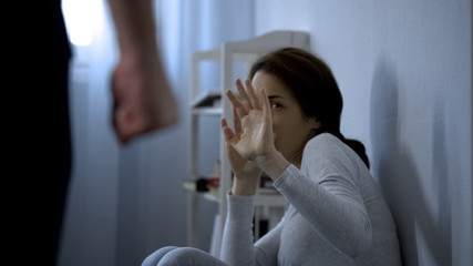 Fototapeta Woman trying to protect herself from fists of enraged husband, assault in family obraz