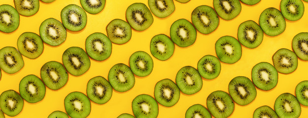 Wall Mural - Green kiwifruit slices in lines with hard shadows on yellow background, flat lay image.