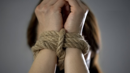 Woman hands tied up with rope, human trafficking, kidnapped woman, hostage