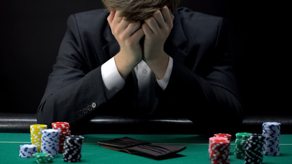 Young devastated businessman losing poker game at casino, gambling addiction