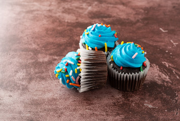 Three blue frosted chocolate cupcakes on a maroon background side view.
