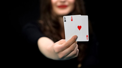 Female hand holding hearts and clubs aces, card pair, advantage, win chance