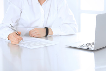 Close-up of female hands with pen over document,  business concept. Lawyer or business woman at work in office