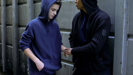 Fototapeta Teenager secretly buying drugs from dealer, disadvantaged city district, crime obraz