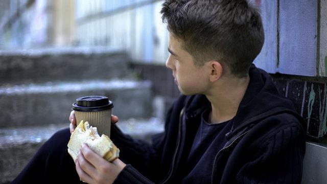 Bullying by senior students, schoolboy eating lunch around school corner alone