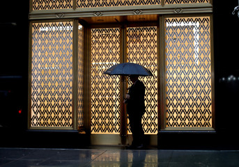 A man is silhouetted in a building's lights as he stands in the rain in Manhattan in New York