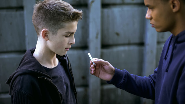 Drug dealer boy treating younger friend with marijuana cigarette, addiction