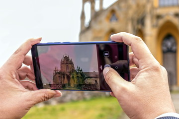 Women hand holding the phone and taking a picture of an old church